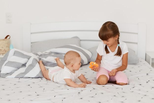 웃고 있는 어린 아이들이 함께 침대에 앉아 노는 실내 사진, 큰 딸이 작은 오렌지색 장난감을 작은 여동생에게 보여주고, 아이들이 밝은 침실에서 침대에서 포즈를 취하고 있습니다.