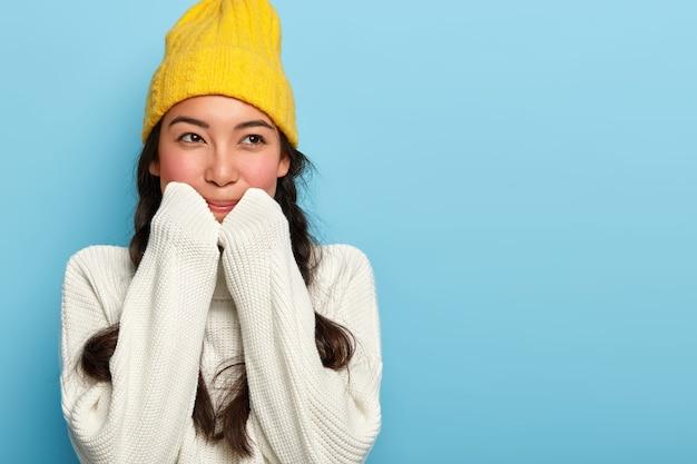 사랑스러운 갈색 머리 여자의 실내 촬영은 노란색 모자와 흰색 스웨터를 입고 꿈꾸는 표정을 가지고 멀리 보이는 파란색 벽에 서