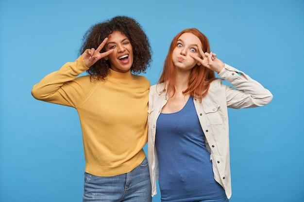 Снимок в помещении: милые веселые девушки веселятся вместе, позируют у синей стены, поднимают на лица знаки мира и радостно смотрят