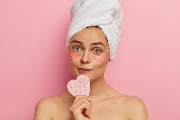 사랑스러운 여성의 실내 샷은 유쾌한 외모, 건강하고 신선한 피부, 심장 모양의 스폰지를 보유하고 있으며, 분홍색 벽 위에 고립 된 미세한 선을 제거하기 위해 눈 패치 아래에 착용합니다. 노화 방지 절차