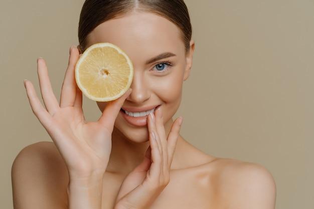Снимок в помещении прекрасной девушки-модели со свежей здоровой кожей, ухоженное тело закрывает глаза долькой апельсина, обнажает плечи.