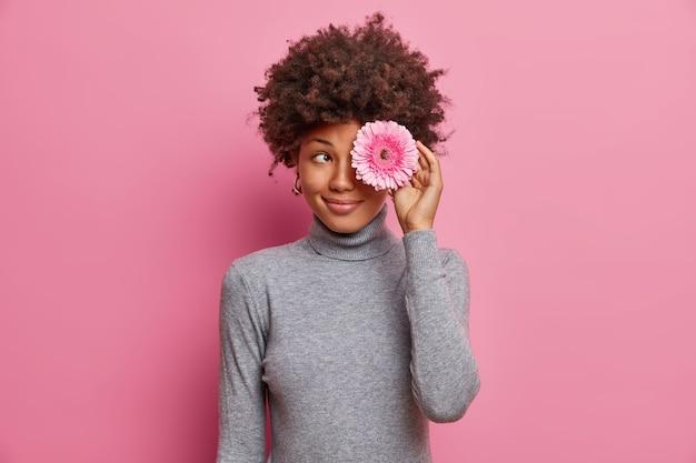 Снимок милой романтичной молодой женщины с нежной улыбкой, держащей цветок над глазами, одетой в повседневную серую водолазку в помещении.