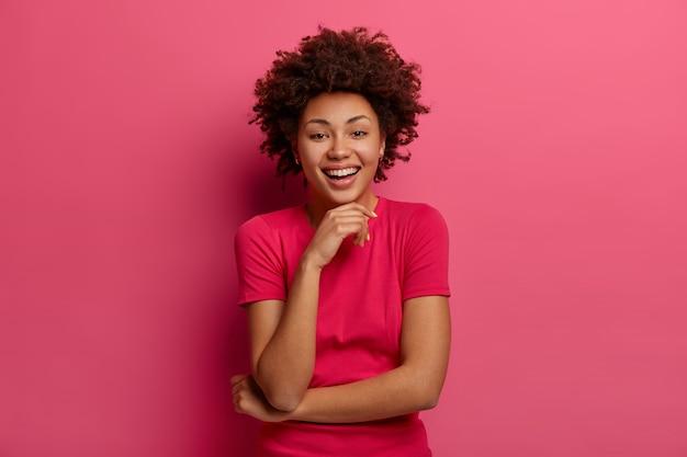 В помещении милая женщина счастливо хихикает, смотрит прямо, держит руку под подбородком, слушает веселую шутку, одетая в повседневную одежду, позирует у розовой стены. концепция эмоций