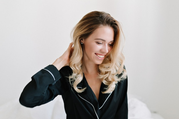 素敵な笑顔でベッドに座っているブロンドの髪の服を着たパジャマと素敵な若い女性モデルの屋内ショット