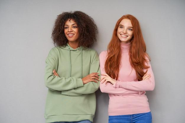 Снимок в помещении: милые молодые позитивные подруги весело смотрят в сторону с очаровательной улыбкой, стоящих у серой стены со скрещенными руками, одетых в удобную повседневную одежду