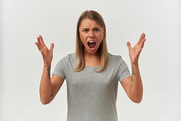 狂った、怒っている若い女性の屋内ショット、カメラに主演し、白で叫びながら彼女の手を上げた