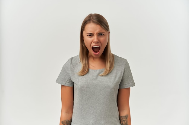 白で叫びながらカメラに主演、怒っている、怒っている若い女性の屋内ショット