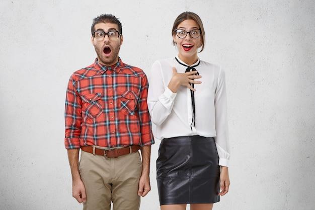 Снимок в помещении: мужчина в старых модных очках и красивая женщина в элегантной одежде с шокированными выражениями