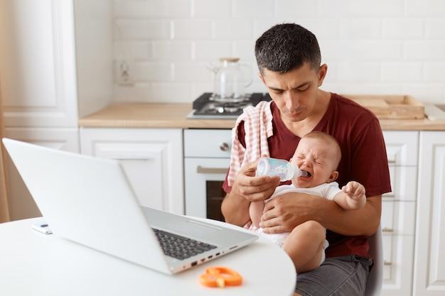 어깨에 수건이 달린 버건디 캐주얼 티셔츠를 입고 아기를 돌보고, 우는 딸에게 병에서 물을 주고, 집에서 노트북으로 온라인 작업을 하는 남자의 실내 사진.