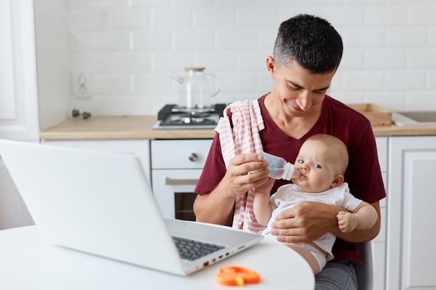 아기 병을 들고 있는 적갈색 캐주얼 티셔츠를 입은 남자, 아버지의 손으로 물을 마시는 어린 딸 또는 아들, 부엌에서 식탁에서 포즈를 취하는 가족의 실내 사진.