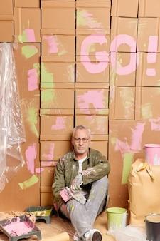 Снимок в помещении: зрелый художник-мужчина сидит на полу и отдыхает после преобразования его домашних красок в стены комнаты, использует все необходимые инструменты, ремонтирует дом, переезжает в новую квартиру, занимается ремонтом.