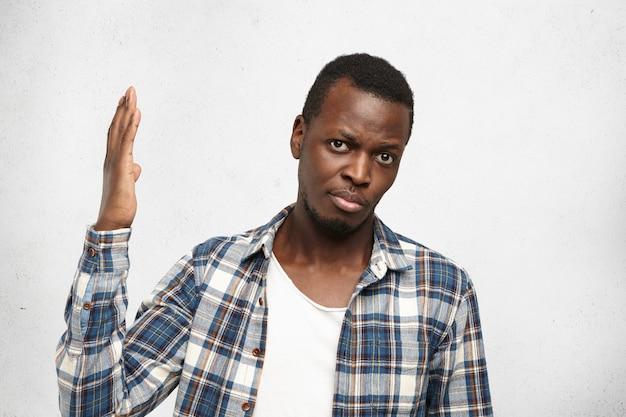 市松模様のシャツを着ている誤解された若いアフリカ系アメリカ人男性の屋内撮影