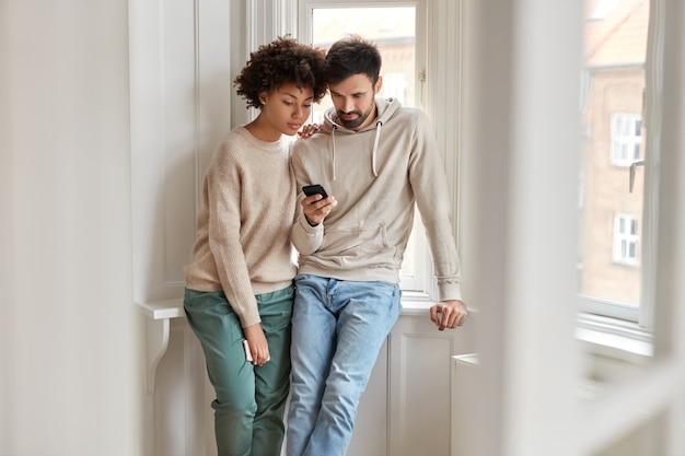 혼혈 여자 친구와 남자 친구의 실내 촬영은 휴대 전화를 통해 온라인으로 비디오를 시청합니다.