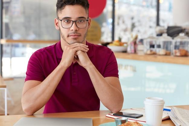 混血の男性の屋内ショットは、あごの下に手を置き、自信を持って表情を見せ、光学メガネをかけ、居心地の良いカフェテリアのテーブルに座って、ラップトップでのリモートワークの後にコーヒーブレイクをします