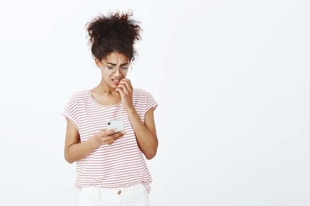 Крытый снимок нервной женщины с афро-прической, позирующей в студии