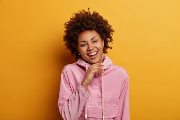 楽観的な縮れ毛のきれいな女性の屋内ショットは、あごの下に手を保ち、直接見て、気分が良く、満足して喜んで立って、カジュアルなスウェットシャツを着て、屋内でポーズをとる