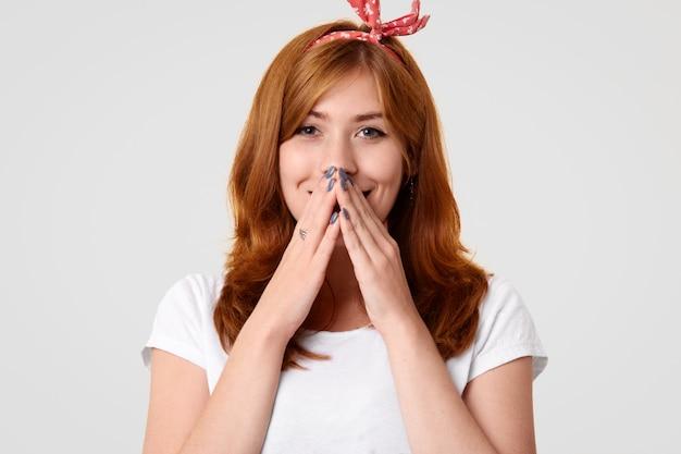 Внутренний снимок оптимистичного европейского женского минуса с руками, хихикает над хорошей шуткой, развлекается с близким забавным другом, который рассказывает анекдоты, носит одежду в стиле ретро, изолированную на белом