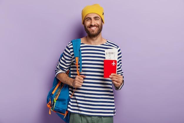 Снимок оптимистичного туриста в помещении, держит паспорт и билеты, несет рюкзак, ожидает полета, готов к отпуску