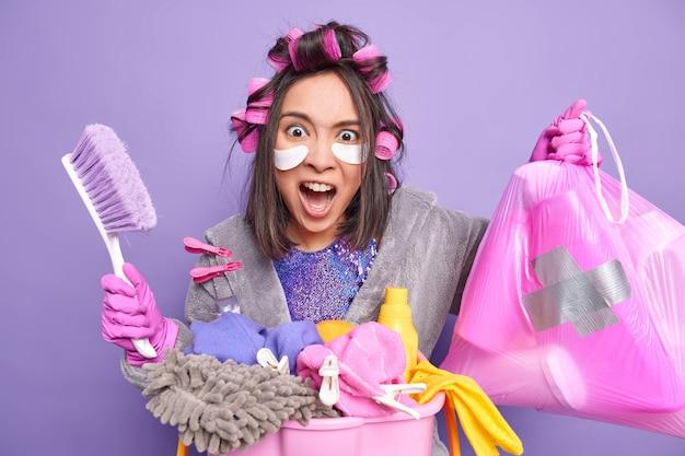 憤慨した主婦の屋内ショットは、家事にうんざりして怒って悲鳴を上げます。バスケットに汚れた洗濯物のブラシとごみ袋のスタックを保持し、髪型を目の下にパスを適用しますドレッシングガウンを着用します