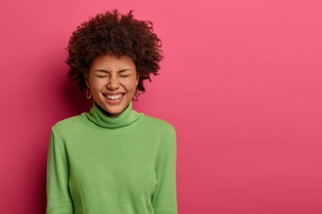 Снимок чрезмерно эмоциональной афро-американской женщины в помещении, смеющейся над забавной шуткой, закрывающей глаза от радости, с выражением лица вне себя от радости.