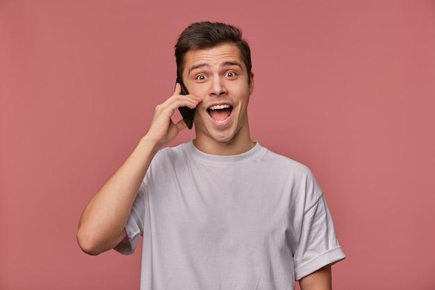 분홍색 배경 위에 포즈를 취하는 회색 티셔츠에 기뻐 갈색 눈동자 젊은 남자의 실내 샷, 전화로 대화를 나누고 유쾌하게 카메라를 찾고