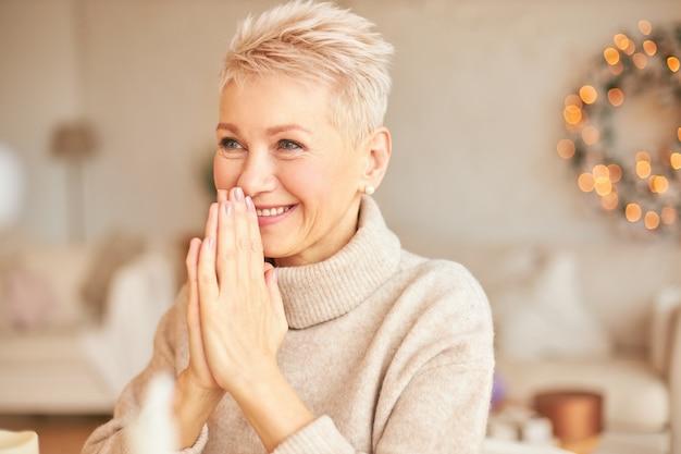 スタイリッシュなセーターを着た、大喜びの陽気な成熟した短い髪の女性の屋内ショットは、彼女の口で手をつないで、大きく笑って、新年の贈り物を受け取り、彼女の興奮を隠すことはできません