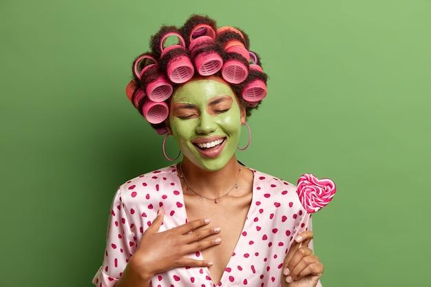 기뻐하는 여성의 실내 샷은 매우 재미있는 일에 긍정적으로 킥킥 웃고, 웃음으로 눈을 감고, 롤리팝을 들고, 깨끗하고 건강한 피부를위한 미용 마스크를 쓰고, 생일에 완벽한 헤어 스타일을 만듭니다.