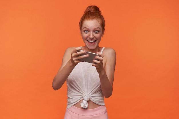 흰색 상단과 분홍색 치마를 입고 폭시 롤빵 헤어 스타일을 가진 기뻐 젊은 여성의 실내 촬영, 손에 휴대 전화로 오렌지 배경 위에 포즈, 흥분된 얼굴로 스마트 폰 게임하기