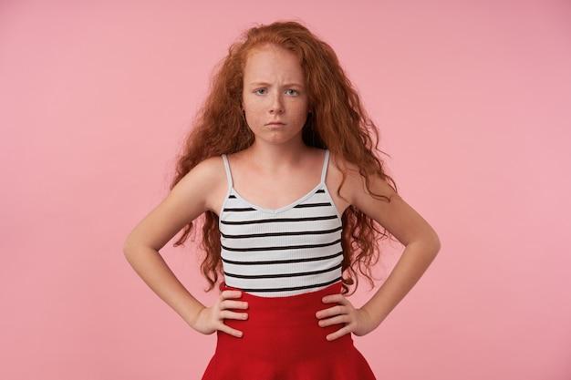 우아한 옷에 분홍색 배경 위에 서있는 긴 곱슬 머리를 가진 잠겨있는 귀여운 여성 십대의 실내 샷, 심각하게 카메라를보고 그녀의 허리에 손을 유지