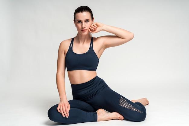 床に座って落ち着いた感情でカメラを見ているスポーツ服を着た物思いにふける黒髪のスポーツウーマンの屋内ショット。女性は健康的なライフスタイルの概念をリードします
