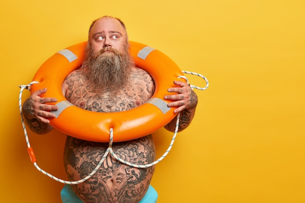 物思いにふける太りすぎの男性の屋内ショットは目をそらし、レクリエーションの準備ができて、救命浮輪と一緒に海で泳ぎ、裸の体を持ち、黄色い壁に隔離され、空白のスペースが脇にあります。安全装置、救助