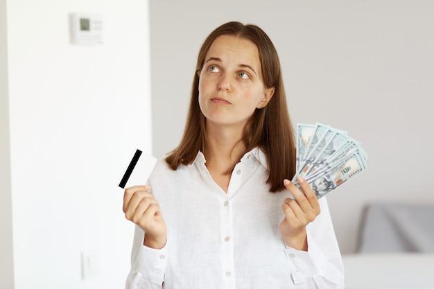 Снимок в помещении: задумчивая женщина в белой рубашке повседневного стиля позирует в светлой комнате дома, смотрит в сторону, держит в руках деньги и кредитную карту и думает, как потратить деньги.