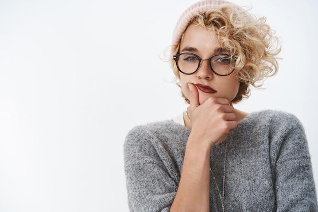 Крытый снимок придирчивой и вдумчивой креативной женщины-дизайнера, создающей новые идеи, в теплой шапке и зимнем свитере с очками, прищурившись, думая, держась за подбородок над белой стеной