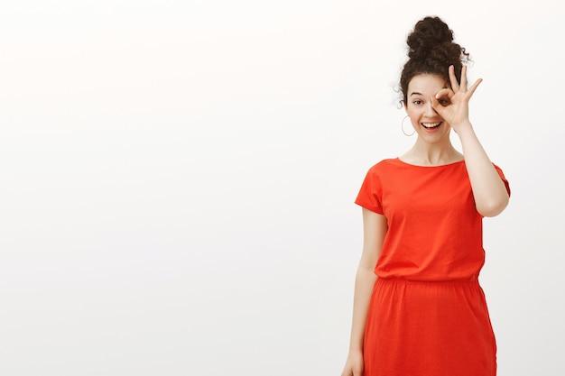 빨간 드레스에 곱슬 머리를 가진 쾌활한 잘 생긴 여성 여성의 실내 촬영은 눈 위에 괜찮거나 승인 제스처를 보이고 광범위하게 웃고 있습니다.