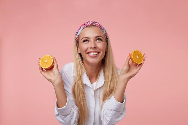 オレンジの半分を手に立って、幸せそうに上向きに見える金髪の女性の屋内ショットは、輝く広い笑顔を持っています
