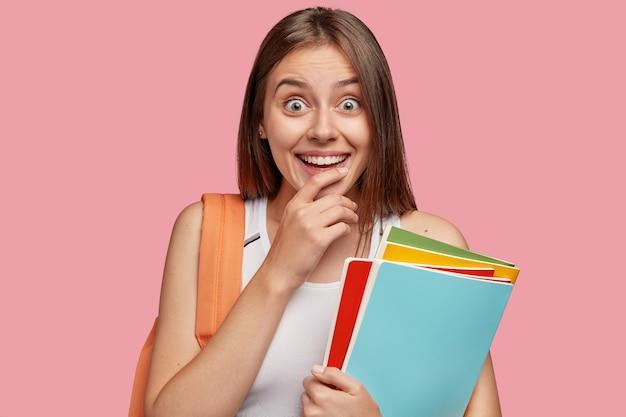 Снимок в помещении: приятная на вид жизнерадостная женщина с зубастой улыбкой, держащая руку за подбородок, выглядит изумленно, одетая в повседневную одежду, несет книги