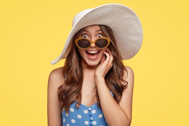 見栄えの良いヨーロッパの女性の屋内ショットは、心地よい笑顔を持ち、夏用の帽子、サングラス、ドレスを着て、忘れられない旅行をして喜んで、黄色い壁の上でポーズをとります。ファッションコンセプト