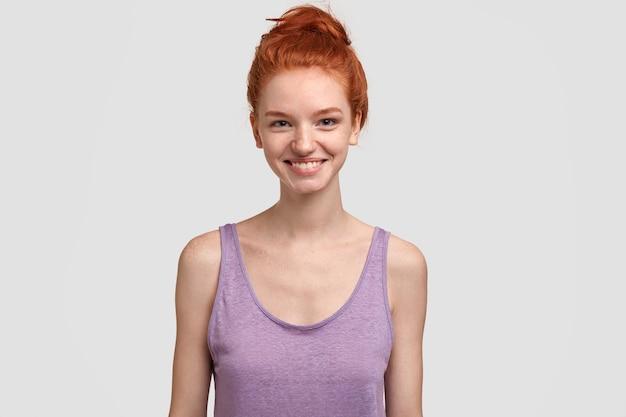 캐주얼하게 옷을 입고 즐거운 찾고 친절한 매력적인 소녀의 실내 샷, 긍정적으로 미소