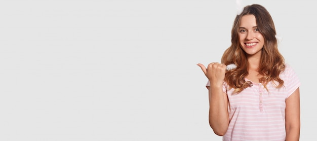 Внутренняя съемка приятной на вид расслабленной женщины рекламирует что-то, показывает пальцем на пустое место для копирования, показывает свободное место для вашего рекламного контента, имеет очаровательную привлекательную улыбку на лице