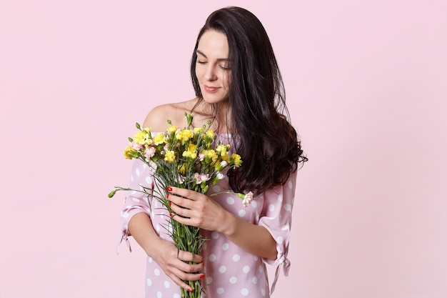 Внутренний снимок довольной темноволосой женской модели держит букет цветов, одетых в модное платье, изолированных на розовом. романтичная привлекательная женщина получает цветы 8 марта