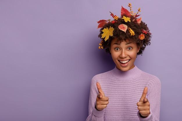 喜んでいる暗い肌の女性の屋内ショットがあなたを指さし、魅力的な広い笑顔を持ち、紅葉が髪に刺さっていて、紫色の壁にモデルがいます