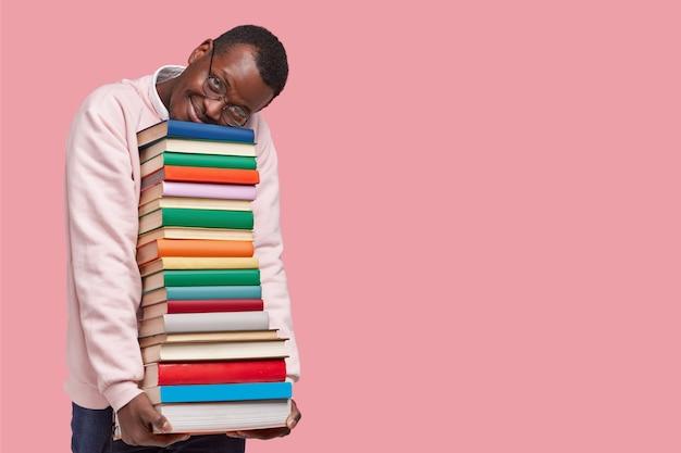 기쁘게 어두운 피부를 가진 남자의 실내 촬영은 캐주얼 스웨터를 입은 책 더미에 몸을 기울이고 둥근 안경을 착용합니다.