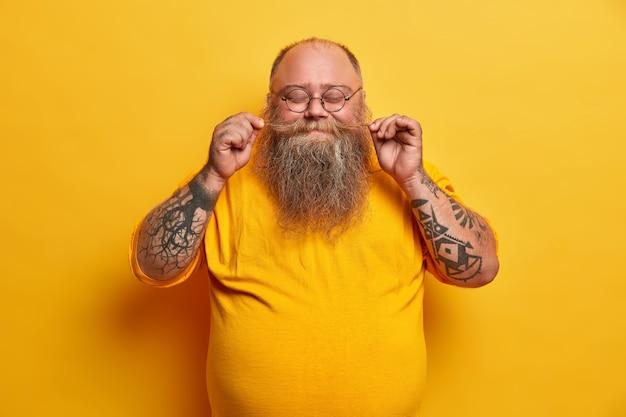 満足しているふっくらとした男の屋内ショットは、口ひげをひねり、厚いあごひげを誇り、目を閉じて立って、心地よく微笑んで、黄色い服を着た入れ墨の腕が丸い小さな眼鏡をかけています
