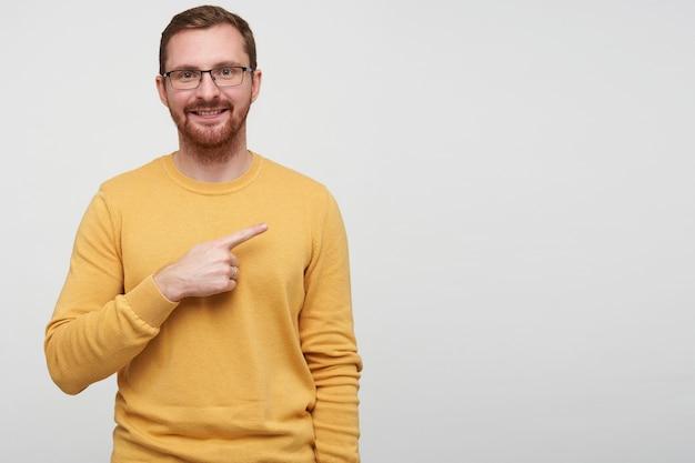 Снимок в помещении довольного коротковолосого молодого брюнет с бородой, весело показывающего в сторону с поднятым указательным пальцем, улыбающегося во время позирования