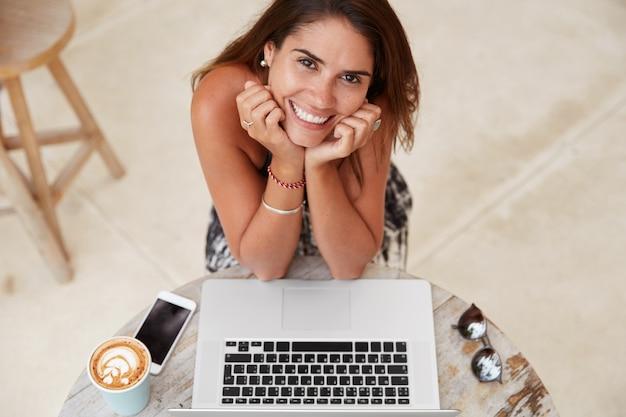 Снимок довольной успешной женщины-копирайтера в помещении, работающей удаленно на портативном компьютере, в окружении современных электронных устройств.