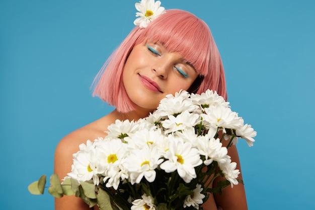 花のトラスを持って、立っている間目を閉じたまま、ボブのヘアカットが愛情を込めて笑っている、喜んでいる若い素敵なピンクの髪の女性の屋内ショット