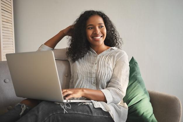 スタイリッシュな服を着て、膝の上にポータブルコンピューターを置いてソファでリラックスし、オンラインで買い物をし、かわいい陽気な笑顔で目をそらしている、ポジティブで魅力的な若いアフリカ系アメリカ人女性の屋内ショット