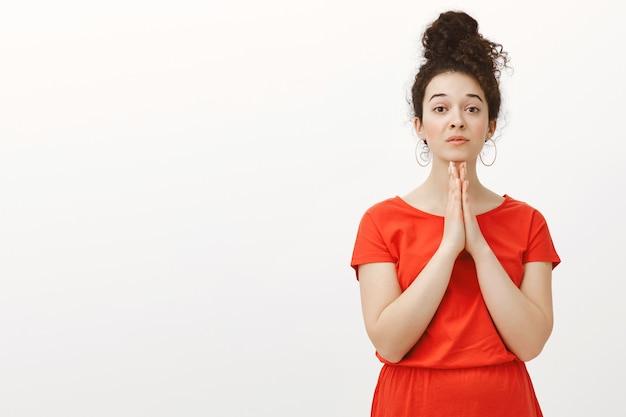 Снимок позитивной милой женщины в красном платье с вьющимися волосами, зачесанными в пучок, в помещении