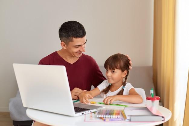 긍정적인 아버지와 어린 딸이 집에서 숙제를 하는 실내 사진, 온라인 수업, 원격 교육을 받는 휴대용 컴퓨터 앞에 앉아 있습니다.