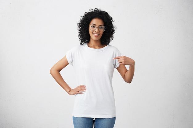 Крытый снимок позитивной дружелюбной молодой женщины смешанной расы в очках, указывая